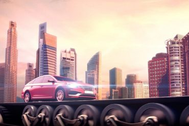 red-car-driving-with-headlights-on-with-city-skyline